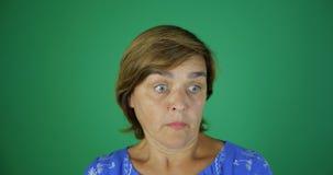 Een donkerbruine vrouw kijkt in verrassing en met bezorgdheid, zijn haar ogen rond gemaakte, langzame motie binnen op het groene  stock video
