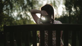 Een donkerbruine vrouw zit op een bank in de zonsondergang stock video