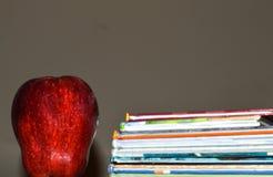 Een donkere foto van een appel naast een stapel van kinderen` s boek voor onderwijs stock afbeelding