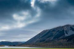 Een donkere, stormachtige mist hulde rotsachtige berg piektorens boven het overgaan van wolken Royalty-vrije Stock Afbeelding