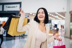 Een donkerharige die gedempte, zachte kleuren dragen houdt kleurrijke, gevormde het winkelen zakkengangen bij exclusief royalty-vrije stock afbeeldingen