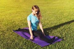 Een donkerharigebus in een sportieve korte bovenkant en gymnastiekbeenkappen maakt een brede streng op de deken want de yogahande royalty-vrije stock foto