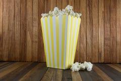 Een doos popcorn op houten achtergrond stock foto