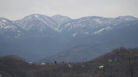 Een dorp op de heuvels tegen de achtergrond van bergen stock video