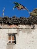 Een dorps Tibetaans huis met een gebedvlag op een vlak dak, de zomer in Zanskar, Noordelijk India Stock Foto's