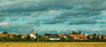 Een dorpsplatteland onder kleurrijke wolken Stock Foto's