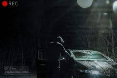 Een dreigende mens die met een kap een auto onderzoeken bij nacht Photoshop geeft om als kabeltelevisie-beeld te kijken uit royalty-vrije stock foto's