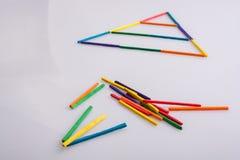 Een driehoek van kleurrijke stokken wordt gemaakt die royalty-vrije stock foto