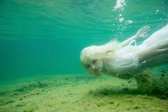 Een drijvende vrouw Onderwaterportret Meisje in witte kleding die in het meer zwemmen Groene mariene installaties, water Royalty-vrije Stock Fotografie