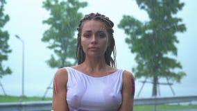 Een droevig aantrekkelijk meisje bevindt zich en schreeuwt in de regen in een natte kleding stock videobeelden