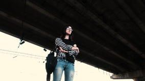 Een droevig beledigd meisje bevindt zich alleen onder de brug stock footage