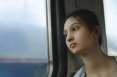 Een droevig jong meisje berijdt een trein royalty-vrije stock foto