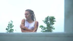 Een droevig meisje bevindt zich en schreeuwt in de regen in een natte kleding stock footage