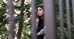 Een droevig meisje loopt achter de rooster en zucht terwijl wat betreft haar overhemd stock video