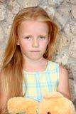 Een droevig meisje met een teddybeer Stock Afbeeldingen