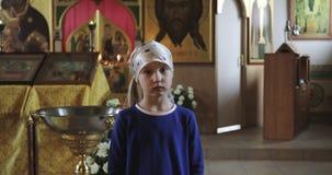 Een droevig meisje in een sjaal en een blauwe kleding bidt in de kerk stock footage