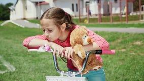 Een droevig meisje zit op een alleen fiets stock video