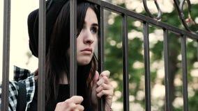 Een droevig wanhopig meisje kijkt door de rooster en het zuchten stock video