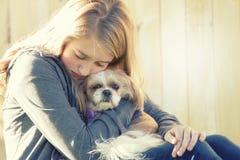 Een droevige of gedeprimeerde tiener die een kleine hond koesteren Stock Foto's