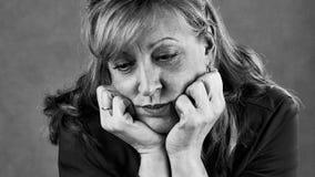 Een droevige gedeprimeerde vrouw in zwart-wit stock fotografie