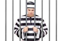 Een droevige gevangene in de staven van de gevangenisholding Stock Foto's