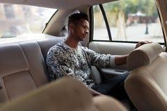 Een droevige jonge mens in binnenland van de auto, op de achterbank, slijtage in vrijetijdskleding, zette zijn hand op de bestuur stock afbeelding