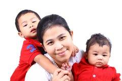 Een droevige jongen, glimlachende moeder, koele zuigeling. Stock Afbeelding