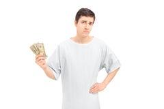 Een droevige mannelijke patiënt in een holdingsamerikaanse dollars van de het ziekenhuistoga Royalty-vrije Stock Afbeelding