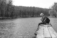 Een droevige mens zit alleen op de pijler door het meer Zwart-wit bos kap op zijn hoofd rugzak in de telefoon van de handengreep stock fotografie