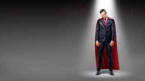 Een droevige zakenman die een rode supermankaap dragen die zich in de schijnwerper met zijn schouders bevinden stortte in royalty-vrije stock afbeeldingen