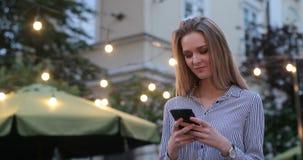Een dromerig romantisch blondemeisje typt bij haar cel telefoon en het glimlachen Avondlichten op de straat op de achtergrond stock videobeelden