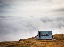 Een dromerige bergscène met een chalet en de wolken behandelen op een moun royalty-vrije stock foto's