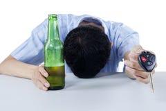 Een dronken bestuurder die een autosleutel aanbieden stock foto