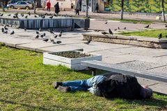 Een dronken mens in slaap op het gras stock afbeelding