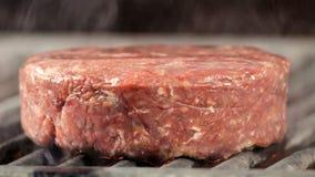 Een dubbele ruwe vleeskotelet ligt op een verwarmde grill, zijaanzichtclose-up van een grote vette kotelet met rundvlees of kalfs stock video