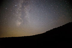 Een duidelijke nachthemel met een heuvel en bomen in de voorgrond Royalty-vrije Stock Foto's