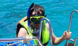 Een duikende mens beklimt aan boord van de boot na het zwemmen Stock Afbeeldingen
