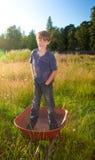 Een echte jonge jongen die zich in een kruiwagen bevinden Stock Foto's