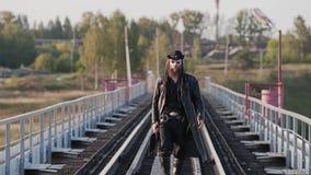 Een echte taaie kerel loopt over de brug naar de camera en bekijkt zijdelings de zonsondergang stock videobeelden