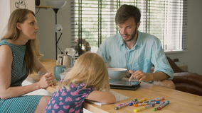 Een echtgenoot die aan zijn iPad werken en aan zijn mooie vrouw bij de keukenlijst spreken Langzame mo stock videobeelden