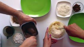 Een echtpaar bereidt snoepjes van condens, kokosnotenspaanders en amandelen voor stock footage