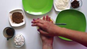Een echtpaar bereidt snoepjes van condens, kokosnotenspaanders en amandelen voor stock video
