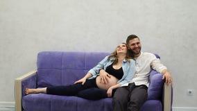 Een echtpaar zit thuis op de laag wachtend op de geboorte van een kind De man streek haar hand over haar stock video