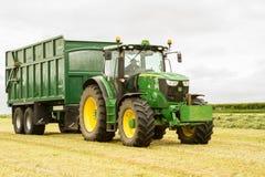Een een groene John Deere-tractor en aanhangwagen van Vestingmuur stock foto's