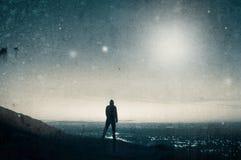 Een eenzaam cijfer die met een kap uit over stadslichten vóór zonsopgang als geheimzinnig licht kijken glanst in de hemel stock fotografie