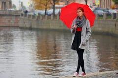 Een eenzaam lopend meisje met rode paraplu royalty-vrije stock foto