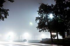 Een eenzame autoaandrijving langs lege stadsstraat bij nacht na regen Stock Fotografie