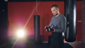 Een eenzame bokser rekt zijn hoofd tijdens hand het verpakken uit stock footage