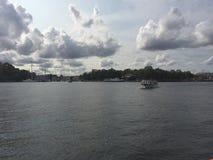 Een eenzame boot die in de rivier kruisen stock afbeeldingen