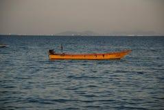 Een eenzame boot in het licht van de het plaatsen zon in de haven van Pattaya stock foto's
